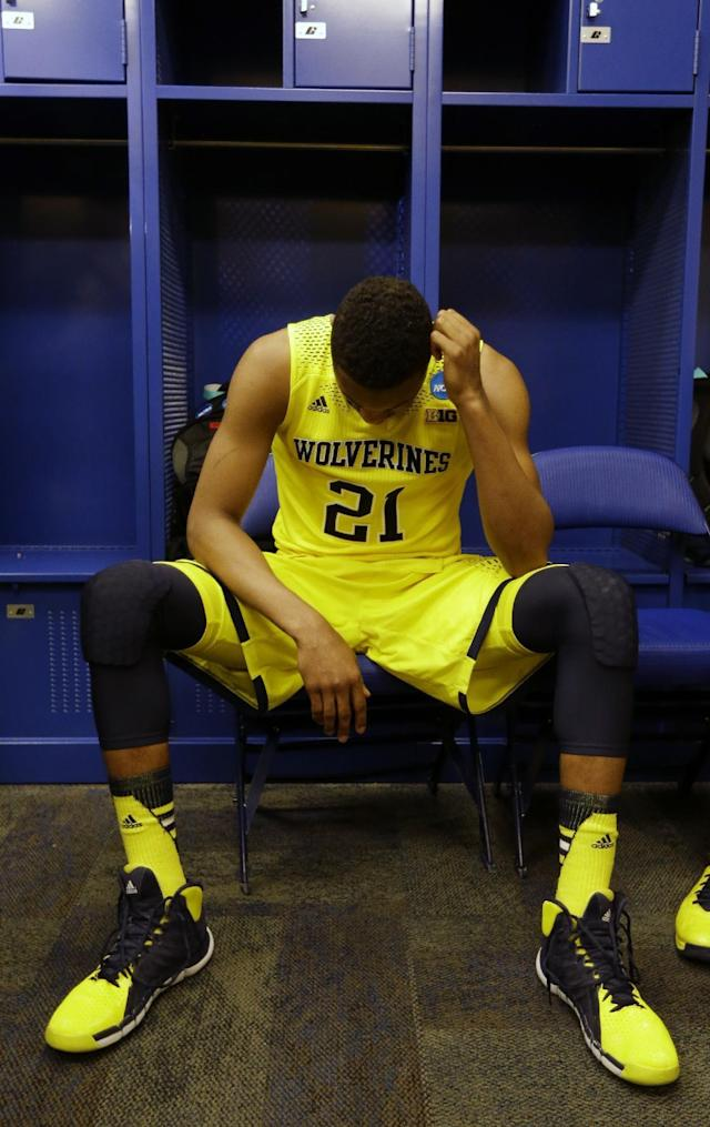 Michigan's Zak Irvin holds his head down in the locker room after an NCAA Midwest Regional final college basketball tournament game against Kentucky Sunday, March 30, 2014, in Indianapolis. Kentucky won 75-72 to advance to the Final Four. (AP Photo/Michael Conroy)