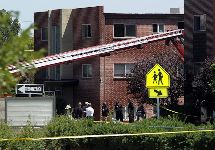 """Firefighters and police gather after an explosion could be heard in front the apartment of shooting suspect James Holmes in Aurora, Colo., Saturday, July 21, 2012. Federal authorities detonated one small explosive and disarmed another inside Holmes' apartment, but several other explosive devices remained, said Aurora police Sgt. Cassidee Carlson. Twelve people were killed and dozens were injured in a shooting attack early Friday at a packed movie theater during a showing of the Batman movie, """"The Dark Knight Rises."""" Police have identified Holmes, 24, as the suspected shooter. (AP Photo/Ed Andrieski)"""