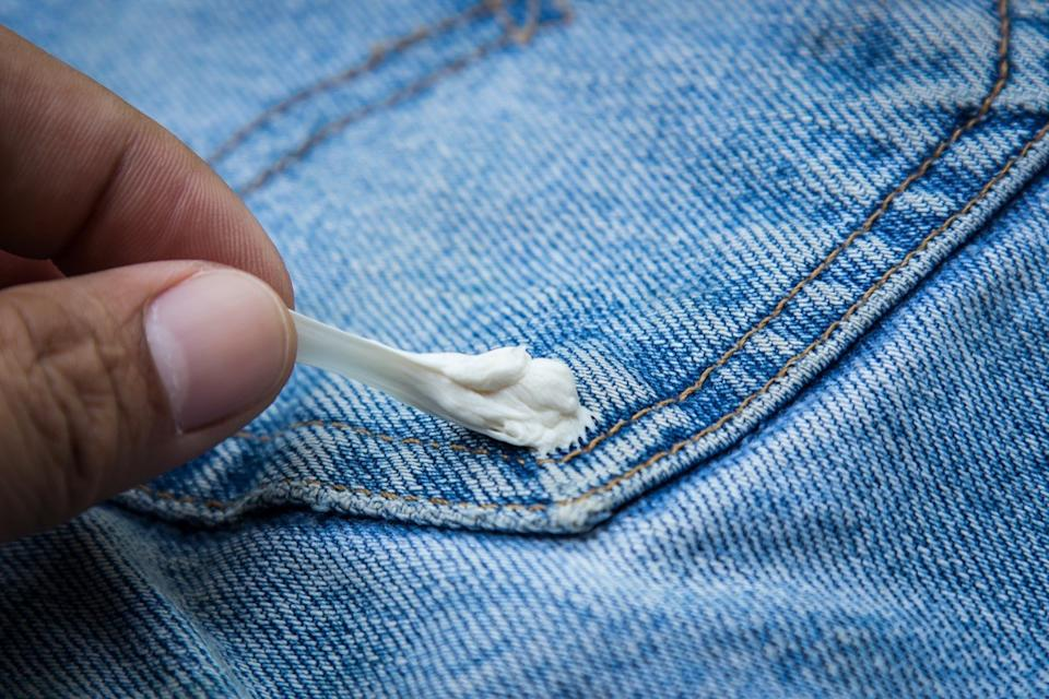 hand removing gum from jeans