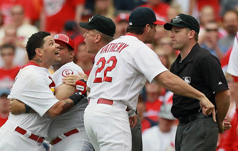 St. Louis Cardinals' Yadier Molina, left, is restrained by his brother, first base coach Bengie Molina, as he protests his ejection by first base umpire Clint Fagan, right, in the third inning of a baseball game against the San Francisco Giants, Sunday, June 2, 2013, at Busch Stadium in St. Louis. Molina was ejected by Fagan for throwing his helmet after grounding out to strand two runners. Cardinals manager Mike Matheny (22) also argues with Fagan and was likewise ejected from the game. Umpire Mike Everitt, third from left, tries to calm matters. (AP Photo/The St. Louis Post-Dispatch, Chris Lee) EDWARDSVILLE INTELLIGENCER OUT; THE ALTON TELEGRAPH OUT Photo by Chris Lee, clee@post-dispatch.com