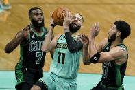 Charlotte Hornets forward Cody Martin (11) drives to the basket past between Boston Celtics guard Jaylen Brown (7) and forward Jayson Tatum during the first half of an NBA basketball game on Sunday, April 25, 2021, in Charlotte, N.C. (AP Photo/Chris Carlson)