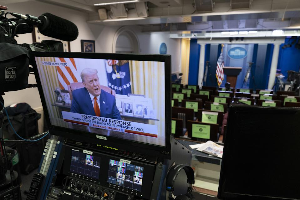 President Donald Trump condemns the violence during a recorded video on a television screen in the press briefing room at the White House. Source: Getty