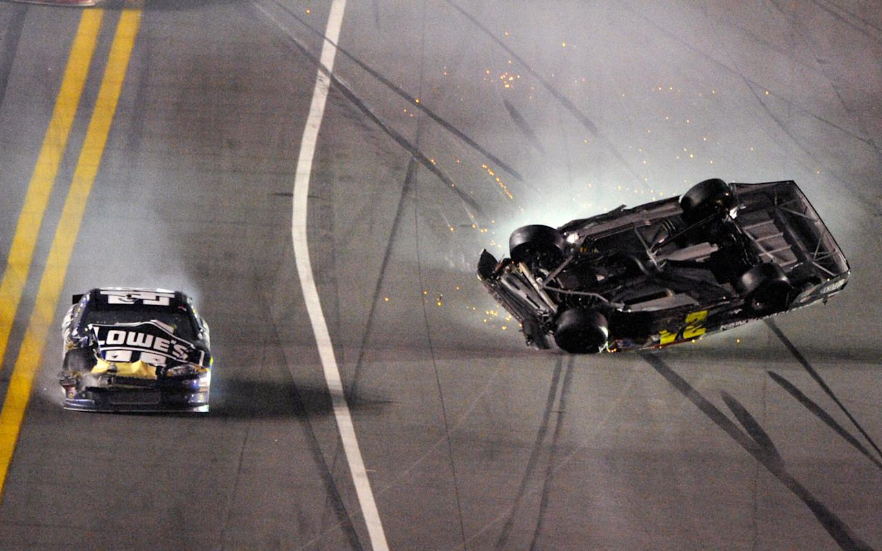 Jeff Gordon's car, right, rolls as Jimmie Johnson drives by during the NASCAR Budweiser Shootout auto race at Daytona International Speedway, Saturday, Feb. 18, 2012, in Daytona Beach, Fla. (AP Photo/Phelan M. Ebenhack)