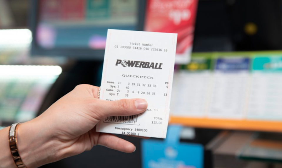 A woman holds a Powerball lottery ticket while standing in a newsagency.