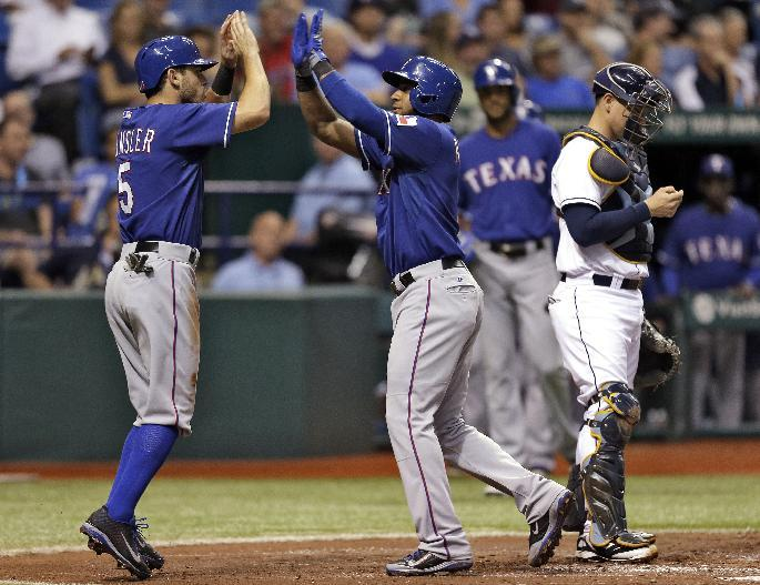 Texas Rangers' Elvis Andrus, center, high fives teammate Ian Kinsler, left, after Andrus hit a third-inning, two-run home run off Tampa Bay Rays starting pitcher Jeremy Hellickson during an MLB American League baseball game Tuesday, Sept. 17, 2013, in St. Petersburg, Fla. Rays' catcher Jose Lobaton is at right. (AP Photo/Chris O'Meara)