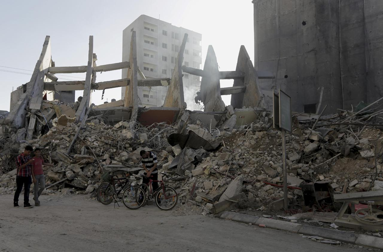 Palestinians walk next to the rubble of the 15-storey Basha Tower that collapsed from early morning Israeli airstrikes in Gaza City, in the northern Gaza Strip, Tuesday, Aug. 26, 2014. Tuesday's strikes leveled the Basha Tower with apartments and offices and severely damaged another high-rise, the Italian Complex, built in the 1990s by an Italian businessman, with dozens of shops and offices. Both buildings were evacuated after receiving warnings of impending strikes. (AP Photo/Adel Hana)