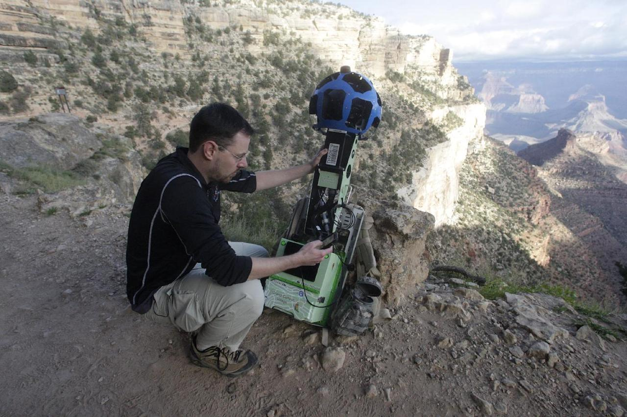 In this Monday Oct. 22, 2012, photo, Google product manager Ryan Falor works with the Trekker during a demonstration for the media along the Bright Angel Trail at the South Rim of the Grand Canyon National Park in Arizona. The search engine giant is using the nearly 40-pound, backpack-sized camera unit to showcase the Grand Canyon's most popular hiking trails on the South Rim and other off-road sites. It's about 4 feet in height when set on the ground, and when worn, the camera system extends 2 feet above the operator's shoulders. (AP Photo/Rick Bowmer)