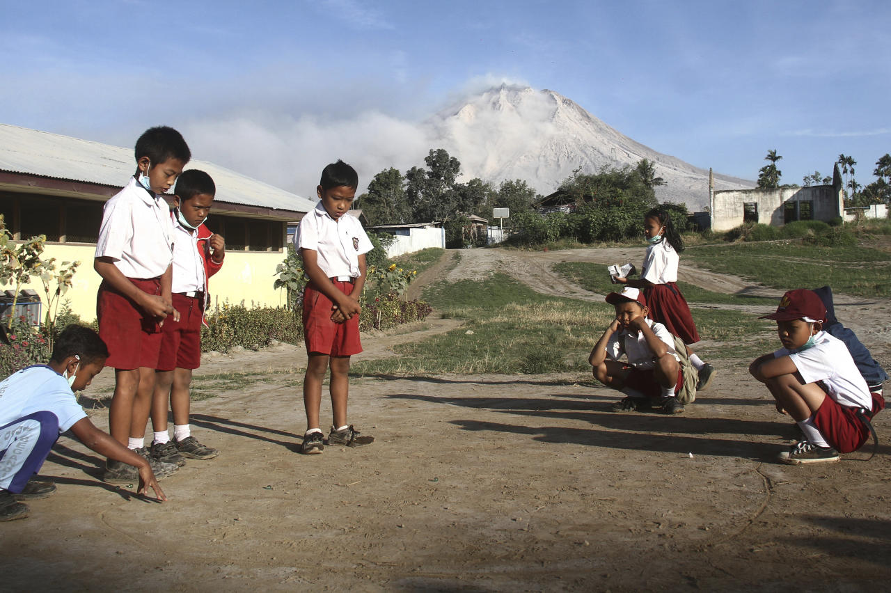 "Students play before the start of their class as Mount Sinabung is seen in the background, at an elementary school in Beganding, North Sumatra, Indonesia, Tuesday, Feb. 20, 2018. Volcanologists say Monday's eruption of the volcano that shot ash 5 kilometers (3 miles) high also ""annihilated"" the mountain's summit. (AP Photo/Ahmad Putra)"