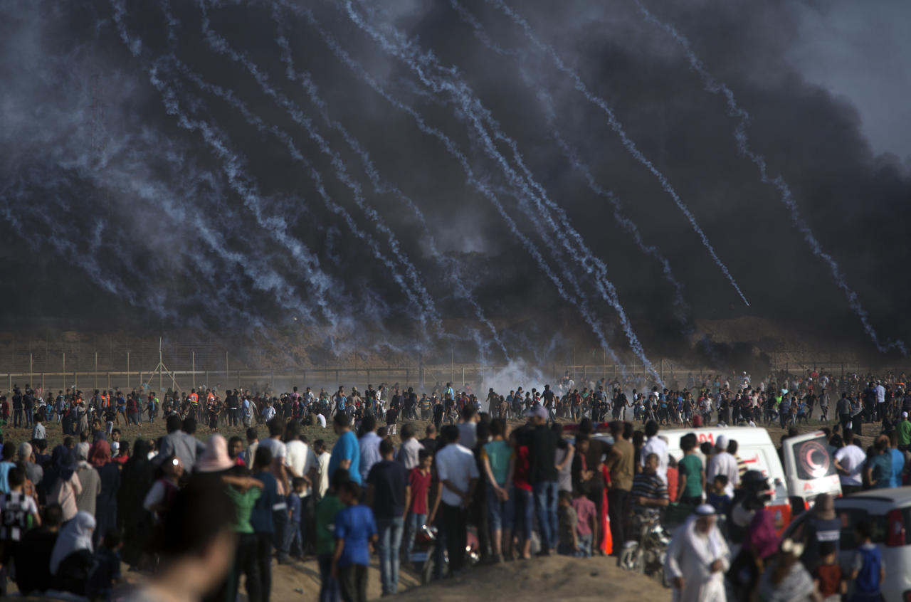 Teargas canisters fired by Israeli troops fall over Palestinians during a protest at the Gaza Strip's border with Israel, Friday, July 13, 2018. Gaza's Health Ministry says a 15-year-old Palestinian has been killed at a border protest by Israeli fire. (AP Photo/Khalil Hamra)