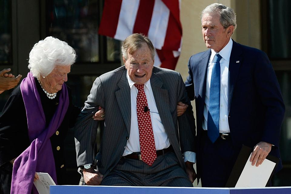 Former first lady Barbara Bush and former President George W. Bush help former President George H.W. Bush rise during the opening ceremony forthe George W. Bush Presidential Center on April 25, 2013, in Dallas, Texas.