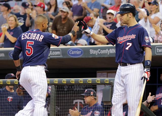 Minnesota Twins' Joe Mauer, right, gives a high-five to Eduardo Escobar who scored on a Danny Santana bunt off Kansas City Royals pitcher Danny Duffy in the third inning of a baseball game, Friday, Aug. 15, 2014, in Minneapolis. (AP Photo/Jim Mone)