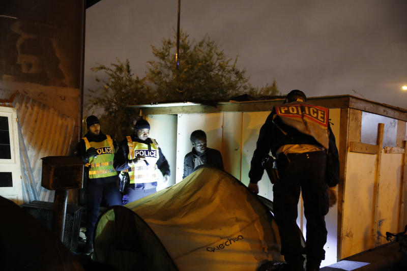 Police officers evacuate a migrant as police forces clear an area Thursday, Nov. 7, 2019 in the north of Paris. Migrant encampments are becoming increasingly visible in the French capital. Police cleared Thursday several thousand people from a northern Paris neighborhood where migrants have repeatedly been removed. They are taken to shelters, and some eventually sent home. (AP Photo/Francois Mori)