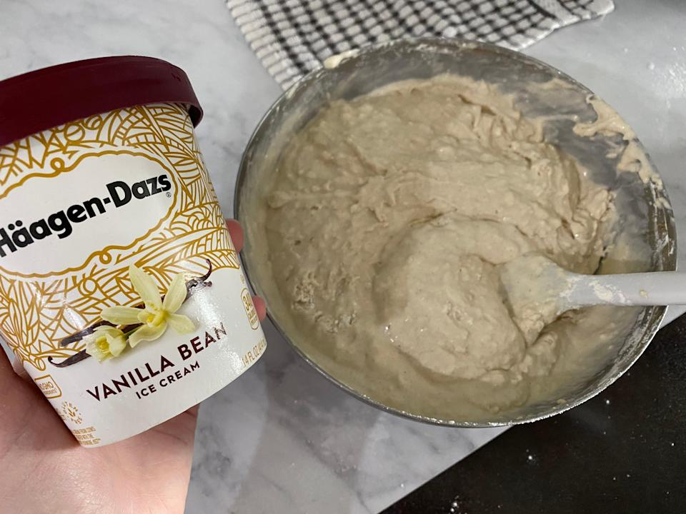 A hand holding a pint of vanilla ice cream beside a bowl of the beige ice cream bread better, which is on a white counter