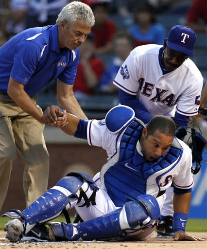 Texas Rangers catcher Yorvit Torrealba is helped to his feet by head athletic trainer Jamie Reed, left, and manager Ron Washington, rear, after he was hit in the head with a piece of a broken bat from Los Angeles Angels' Albert Pujols during the first inning of a baseball game Friday, May 11, 2012, in Arlington, Texas. Torrealba continued playing. (AP Photo/Tony Gutierrez)