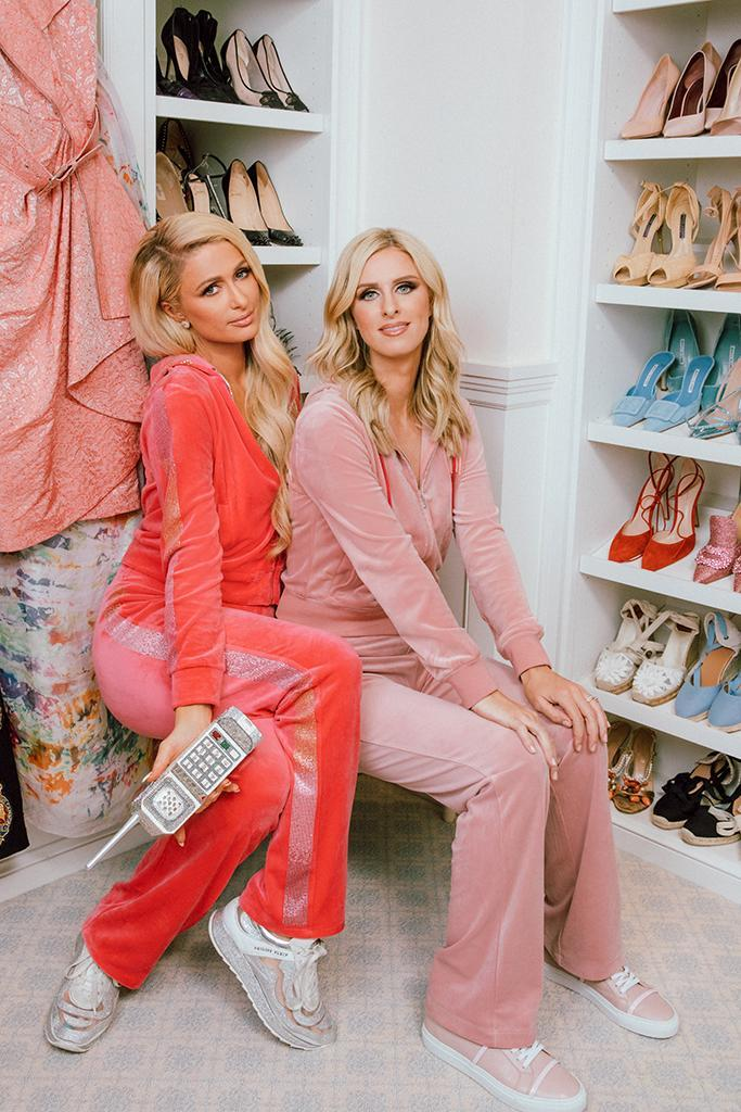 Paris and Nicky in matching customized Juicy Couture velour tracksuits. Paris wears a pair of Philipp Plein crystal-studded sneakers and carries her mother Kathy's crystal-studded cordless phone clutch. Nicky wears Malone Souliers Deon leather sneakers. - Credit: CAMRAFACE