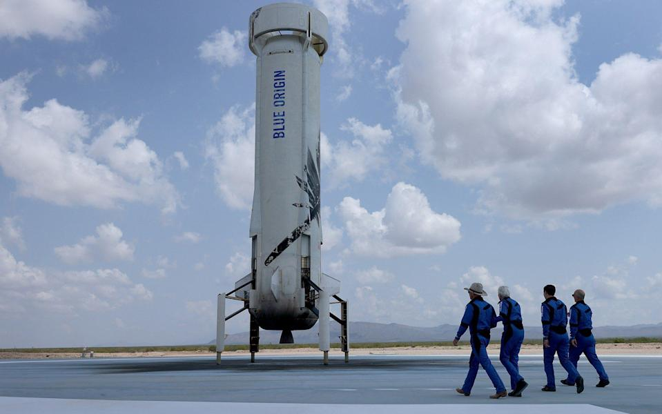 Jeff Bezos, Wally Funk, Oliver Daemen, and Mark Bezos walk near the Blue Origin booster after flying into space in the Blue Origin New Shepard rocket - Joe Raedle/Getty Images North America