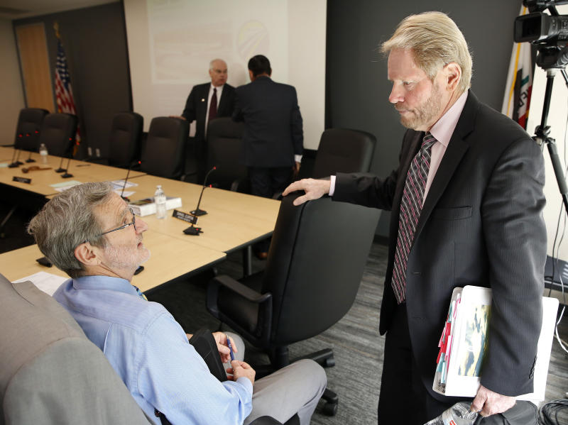 Daniel Curtin, left, a member of the California- High Speed Rail Authority Board of Directors, talks with Thomas Richards, vice chairman of the board of directors, following a board meeting Tuesday, May 21, 2019, in Sacramento, Calif. California has sued to block the Trump Administration from cancelling nearly $1 billion for the state's high-speed rail project. The lawsuit field Tuesday May 21, 2019 comes after the administration revoked the funding last week. (AP Photo/Rich Pedroncelli)