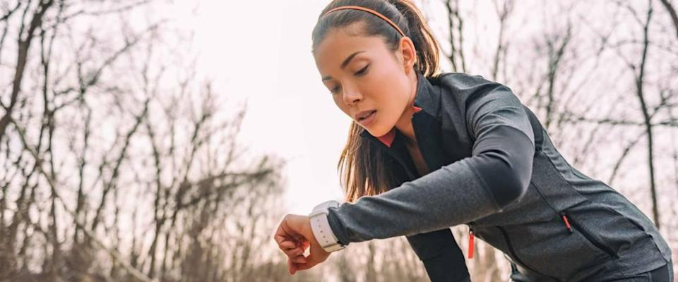 woman running on a trail, looking at smart watch, bent over