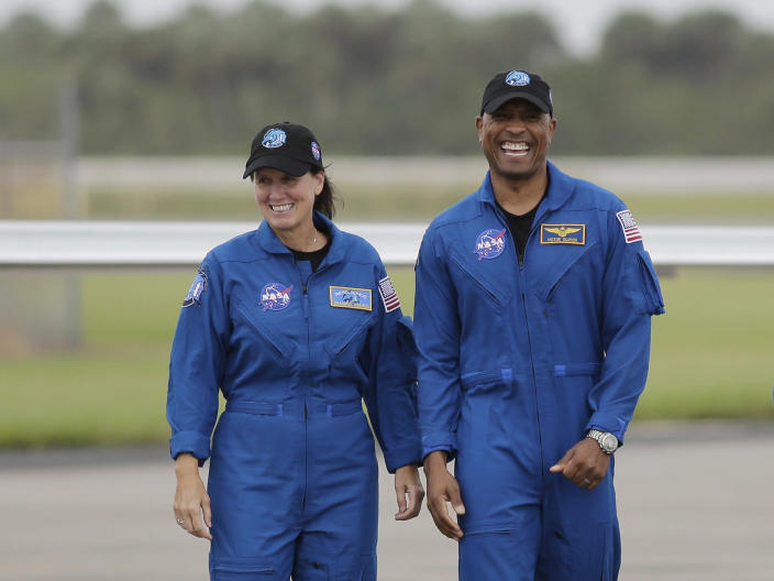NASA Astronauts Shannon Walker, left, and Victor Glover walk from their airplane after arriving at the Kennedy Space Center, Sunday, Nov. 8, 2020, in Cape Canaveral, Fla. Four astronauts will fly on the SpaceX Crew-1 mission to the International Space Station scheduled for launch on Nov. 14, 2020. (AP Photo/Terry Renna)