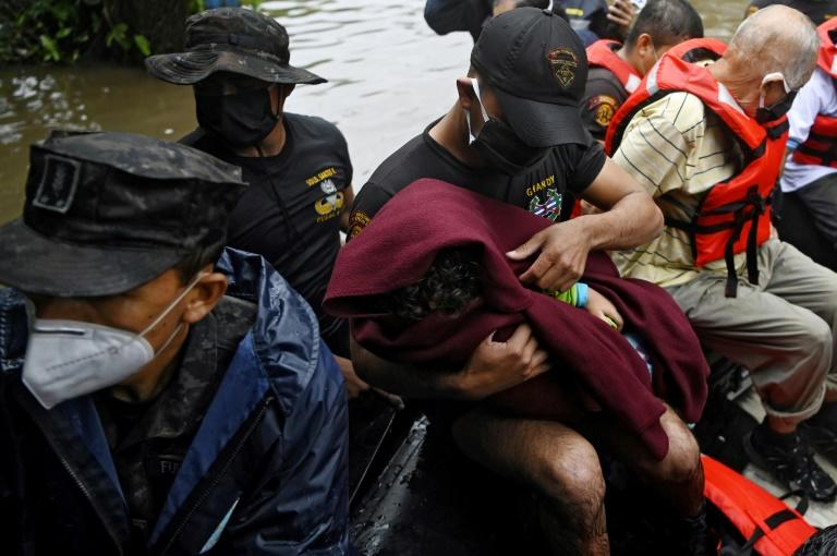A soldier wraps a child in a blanket during an operation to assist flood victims in Santa Lucia colony in Ilopango, El Salvador, during Tropical Storm Amanda, on May 31, 2020