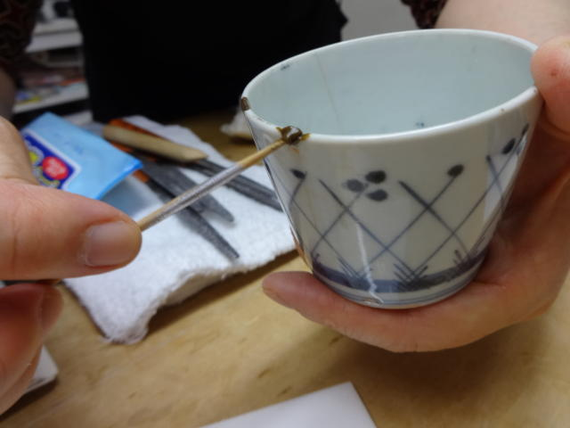 This Nov. 11, 2018 photo shows the first step in the traditional method of Kintsugi where a chip is filled in with layers of plant resin at the Kuge Crafts workshop in Tokyo. Kintsugi is an ancient Japanese method of repairing broken pottery with gold that creates a new work of art. (Linda Lombardi via AP)