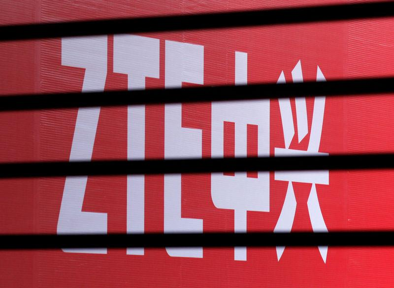 FILE PHOTO - The company logo of ZTE is seen through a wooden fence on a glass door during the company's 15th anniversary celebration in Beijing