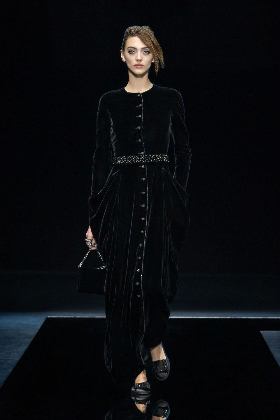"""<p>Giorgio Armani is forever soft and subtle—precise, but never harsh. His particular presentation of femininity is brought to life with ruffles and petals and peeks of skin (jackets that flare open over the navel and long skirts layered over shorter ones to let legs emerge mid-stride). Rich velvets and rippling silks coyly suggest you touch without demanding it, a demure attitude upheld even by the more must-touch crystals and spiral ruffles. Entitled """"Nocturnal,"""" it seems fair to read the collection's palette as a sign that we're collectively emerging from what's felt like one very long night. Every hue of blue was used, including the inkiest iteration of a midnight sky, and spots of blush warmed things up much like the first tentacles of sun do upon the dawning of a new day. Lovely and surefooted, it's a wonderful forecast for the future.<em>—Leah Melby Clinton</em></p>"""
