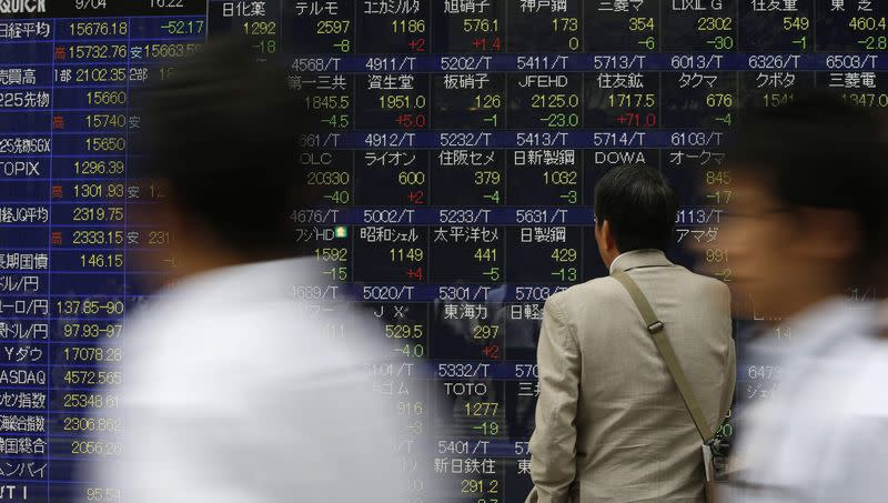 A man looks at an electronic stock quotation board outside a brokerage in Tokyo September 4, 2014. REUTERS/Issei Kato