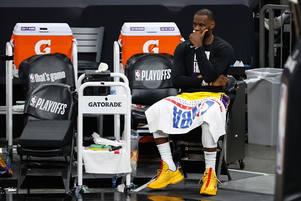 LeBron James watches his Los Angeles Lakers get blown out from the bench in Game 5 of their first-round playoff series.  (Christian Petersen/Getty Images)