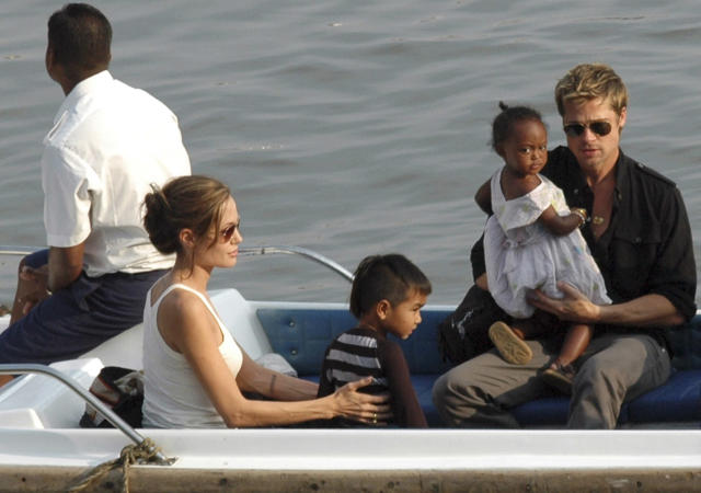 Hollywood star Brad Pitt (R) carries adopted daughter Zahara while Angelina Jolie (2nd L) sits with adopted son Maddox during a boat ride in Mumbai November 18, 2006. REUTERS/Stringer (INDIA)