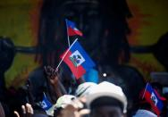Demonstrators hold Haiti's national flags during a protest against the government of President Jovenel Moise, in Port-au-Prince
