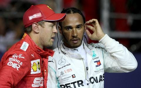 Second place qualifier Lewis Hamilton of Great Britain and Mercedes GP and third place qualifier Sebastian Vettel of Germany and Ferrari talk in parc ferme during qualifying for the F1 Grand Prix of Singapore at Marina Bay Street Circuit on September 21, 2019 in Singapore - Credit: Getty Images