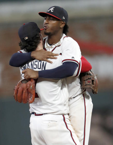 Atlanta Braves' Ozzie Albies, right, hugs Dansby Swanson (7) after defeating the Philadelphia Phillies 8-3 in a baseball game Thursday, Sept. 20, 2018, in Atlanta. (AP Photo/John Bazemore)
