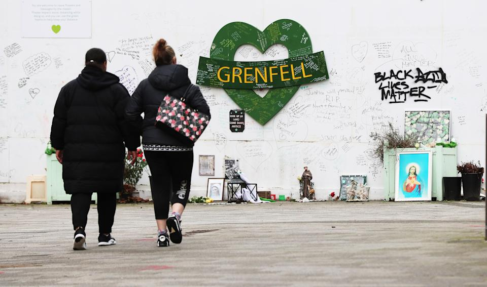 Two women walk towards the Grenfell Memorial Wall in the grounds of Kensington Aldridge Academy. Picture date: Tuesday February 16, 2021. (Photo by Jonathan Brady/PA Images via Getty Images)
