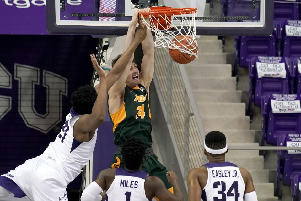 North Dakota State forward Rocky Kreuser (34) dunks the ball after getting through TCU defenders Kevin Samuel, left, Mike Miles (1) and Kevin Easley in the second half of an NCAA college basketball game in Fort Worth, Texas, Tuesday, Dec. 22, 2020. (AP Photo/Tony Gutierrez)