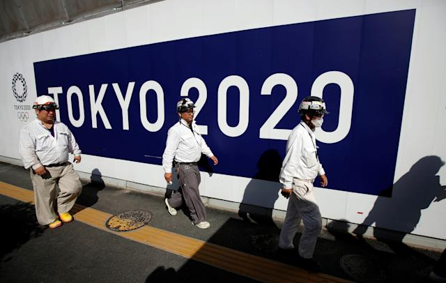 Construction workers walk past at a construction site of a building displaying Tokyo 2020 Olympics emblem and logo in Tokyo, Japan on May 23, 2017. (Reuters)