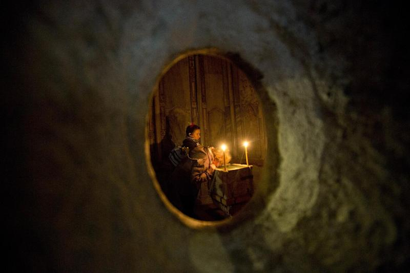 Faithful visit the renovated Edicule in the Church of the Holy Sepulchre, traditionally believed to be the site of the crucifixion of Jesus Christ, in Jerusalem's old city Monday, Mar. 20, 2017. A Greek restoration team has completed a historic renovation of the Edicule, the shrine that tradition says houses the cave where Jesus was buried and rose to heaven. (AP Photo/Sebastian Scheiner)