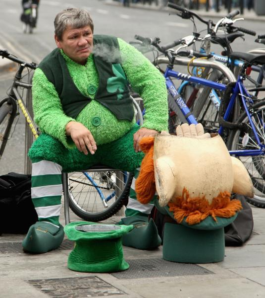A street performer dressed as a leprechaun smokes a cigarette as he takes a break in Dublin, Ireland.