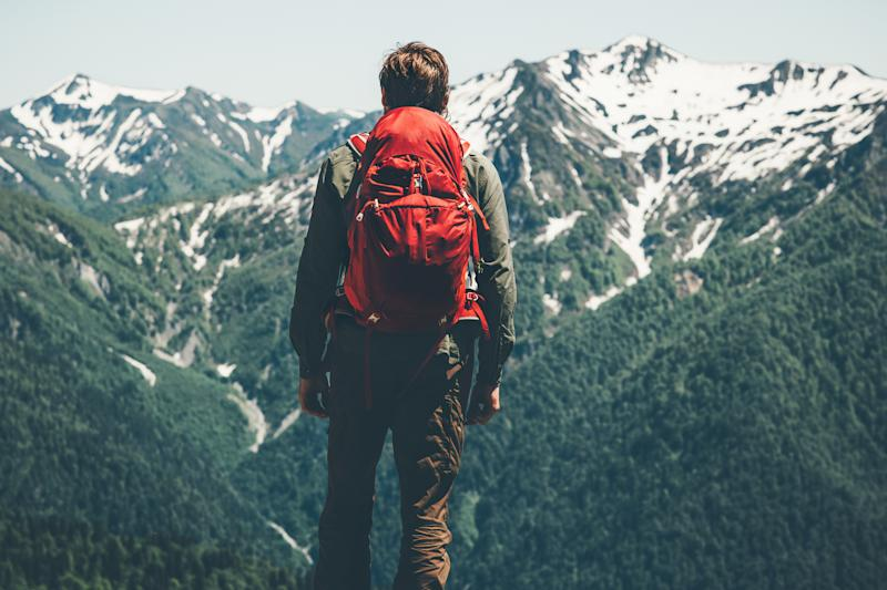 Man hiking in mountains with red backpack