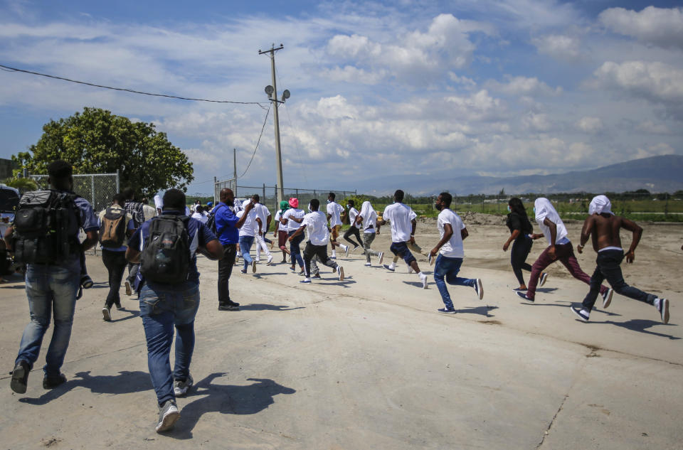 Haitians deported from the United States run back to the tarmac to try to get on the same plane they were deported in, in an attempt to return to the United States, at the Toussaint Louverture airport in Port-au-Prince, Haiti Tuesday, Sept. 21, 2021 (AP Photo/Joseph Odelyn)
