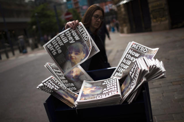 <p>A woman picks a newspaper reporting the news on the suicide attack at a concert by Ariana Grande that killed more than 20 people as it ended Monday night in central Manchester, Britain, May 24, 2017. (Photo: Emilio Morenatti/AP) </p>