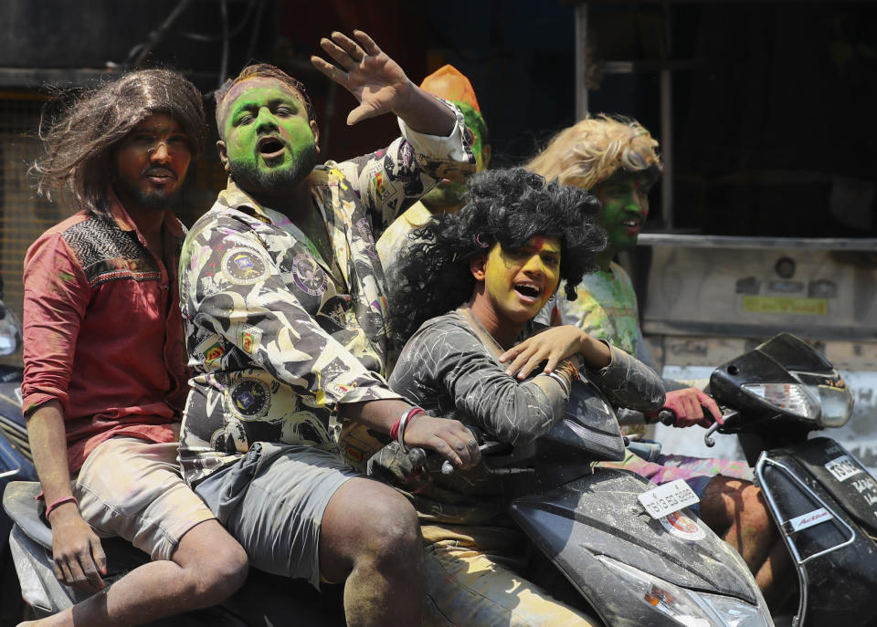 Revelers with their faces smeared with colored powder ride on motor bikes during Holi festivities in Hyderabad, India, Monday, March 29, 2021. (AP Photo/Mahesh Kumar A.)