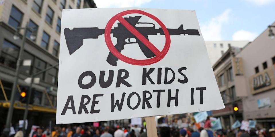 """People walk with signs against assault rifles during """"March for Our Lives"""", an organized demonstration to end gun violence, in downtown Los Angeles, California, U.S., March 24, 2018."""