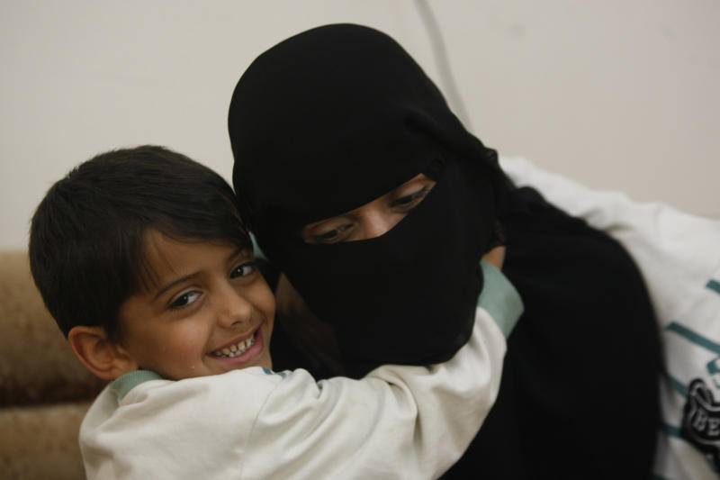 In this photo taken on Friday, Feb. 14, 2014, Hamza, 6, left, hugs his mother Abeer al-Hassani whose two brother were killed in a US drone strike last year and a third brother was killed in fighting against government troops in 2012. All three brothers had joined al-Qaida in Yemen before their deaths. (AP Photo/Hani Mohammed)