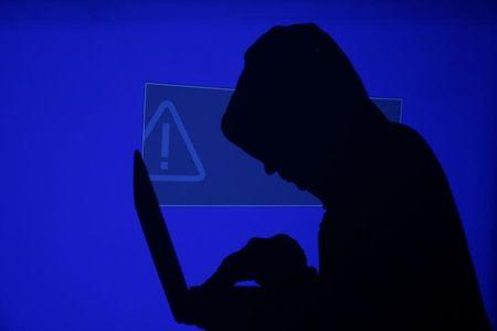 Hooded man holds laptop computer as blue screen with an exclamation mark is projected on him in this illustration