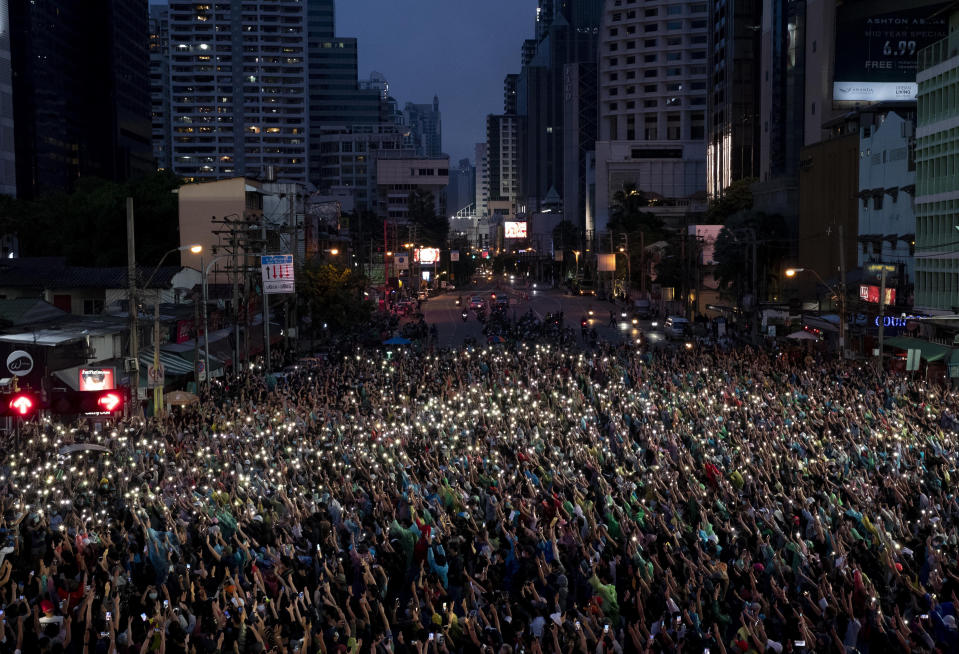 Pro-democracy supporters wave their mobile phones with flash on during a protest rally at an intersection in Bangkok, Thailand, Sunday, Oct. 18, 2020. Pro-democracy activists in Thailand launched their fifth straight days of protests on Sunday, scheduling demonstrations not just in the capital but also at several other locations around the country. (AP Photo/Gemunu Amarasinghe)