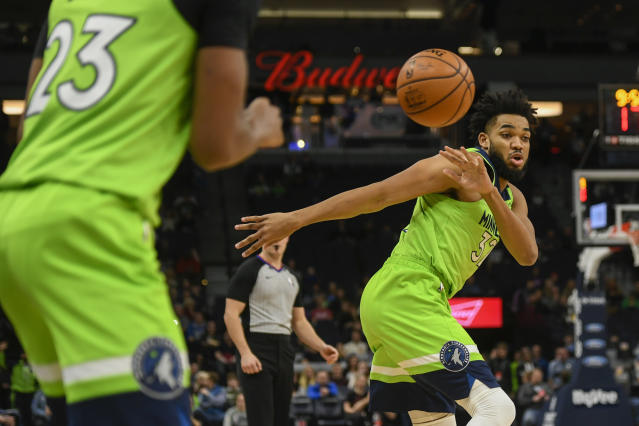 Minnesota Timberwolves center Karl-Anthony Towns, right, passes the ball to Minnesota Timberwolves guard Jarrett Culver during the first half of an NBA basketball game against the Oklahoma City Thunder Saturday, Jan. 25, 2020, in Minneapolis. (AP Photo/Craig Lassig)