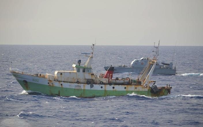 The Italian fishing boat Aliseo was fishing north of the Libyan coast when it was hit by shots fired by a Libyan patrol vessel,seen in the background - MarinaMilitare/DAPRESS / SplashNews.com