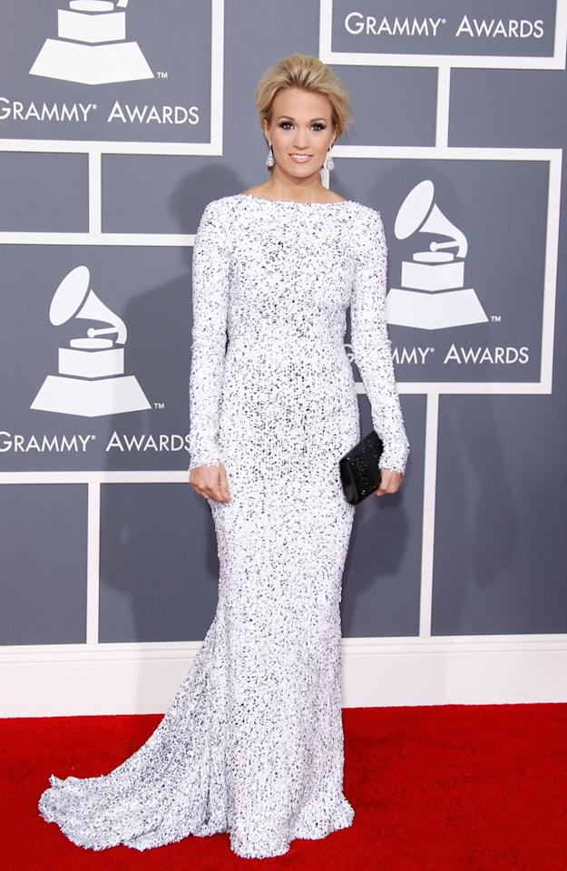 "Carrie Underwood shows off her figure in a Gomez-Gracia lace gown at the 54th Annual GRAMMY Awards on February 12, 2012.<br><br>When asked by <em>People Stylewatch</em> what her red carpet secrets were, she said, ""a stylist and Spanx!"""