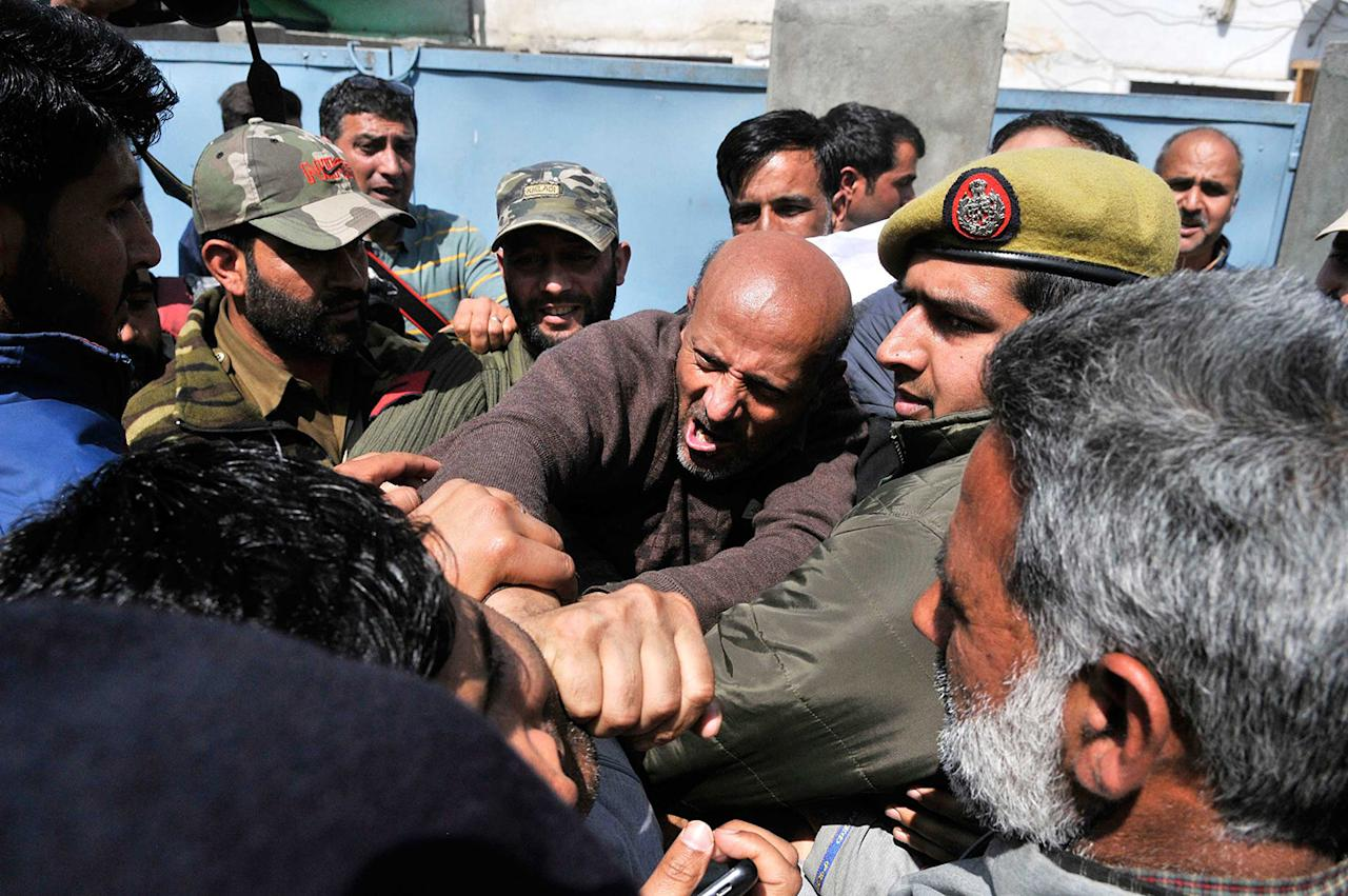 <p>Engineer Rashid, center, an independent member of the Jammu and Kashmir state assembly and leader of Awami Ittihaad party (AIP), shouts slogans as Indian police men stop him from taking a protest march against the killing of civilians in Srinagar, Indian controlled Kashmir, Wednesday, March 29, 2017. Shops and business establishment remained closed Wednesday in Indian-controlled Kashmir after separatists called for a strike against the killing of three civilians during anti-India protests near the site of a gunbattle on Tuesday. (Waseem Andrabi/Hindustan Times via Getty Images) </p>